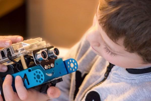 Enfant qui découvre la robotique en jouant avec un robot mobile