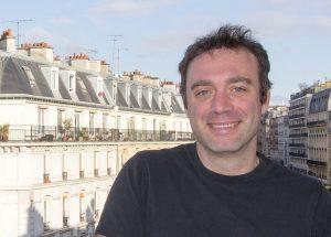 Photo de Francesco, fondateur et gérant des Ingéniaux, devant un quartier de Paris