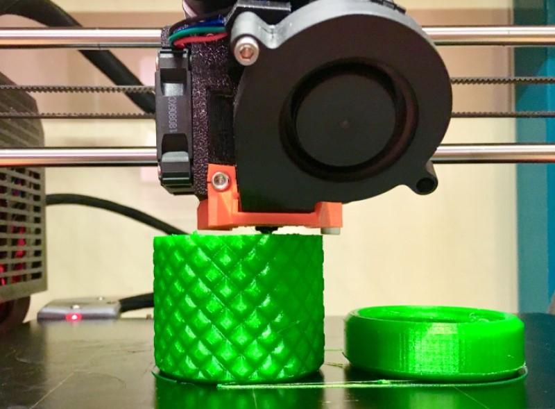 L'imprimante 3D termine l'impression d'une boite verte et son bouchon