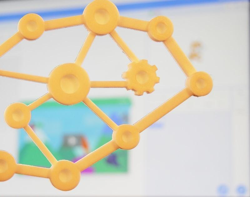 Logo des Ingéniaux, imprimé en 3D, sur un fond avec une scène Scratch