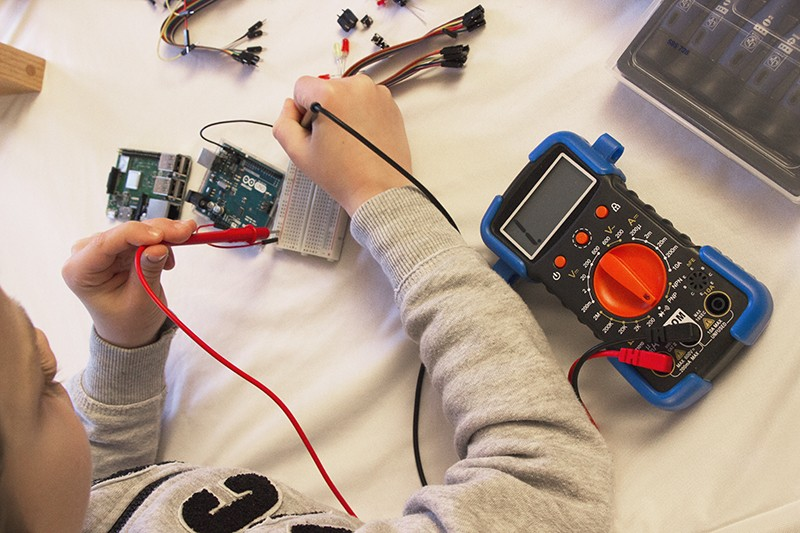 A child uses a multimeter on an Arduino board